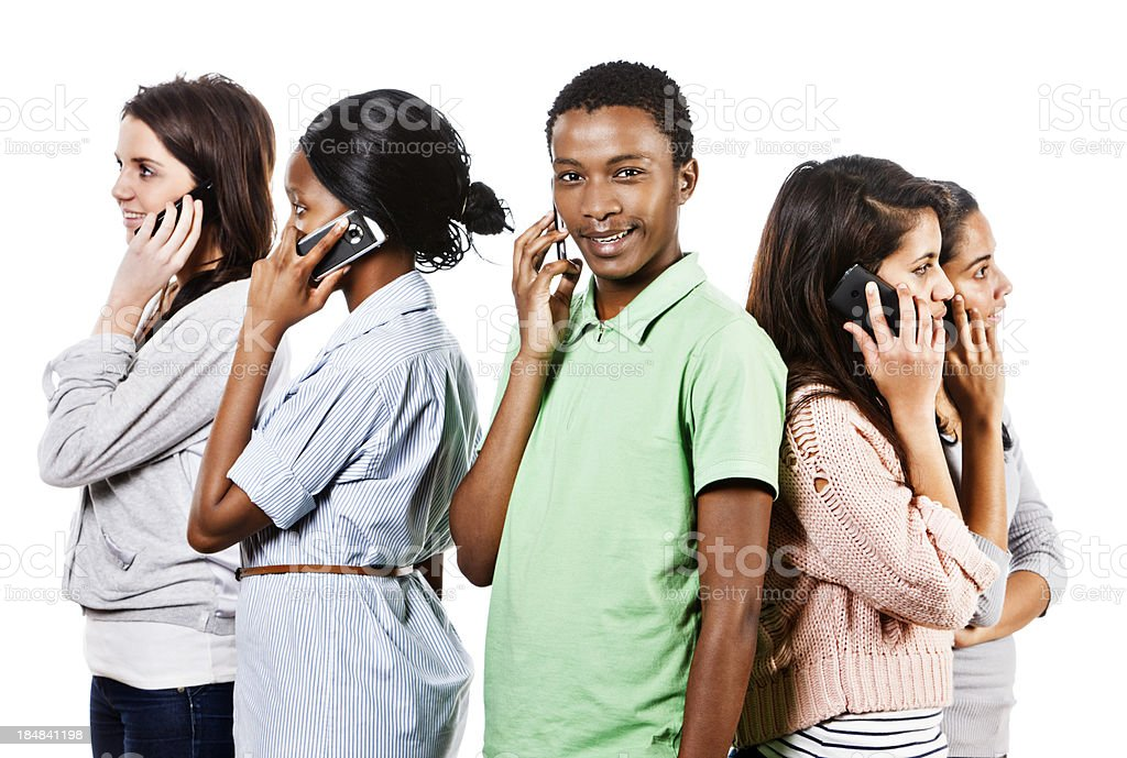 Five young people back-to-back chatting on mobile phones stock photo