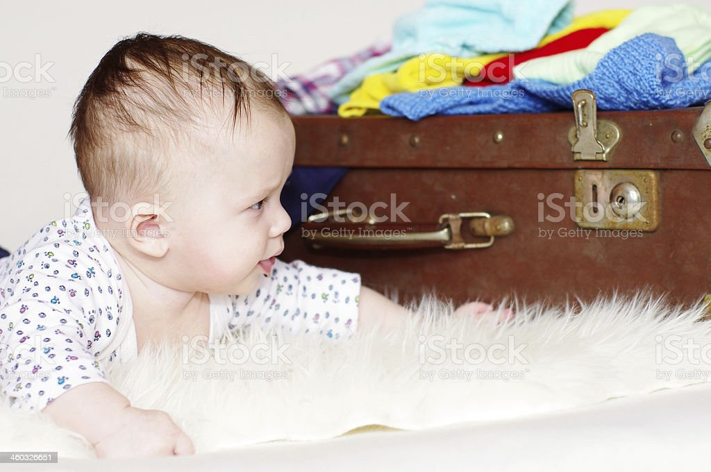 five-months baby looks at an old suitcase stock photo