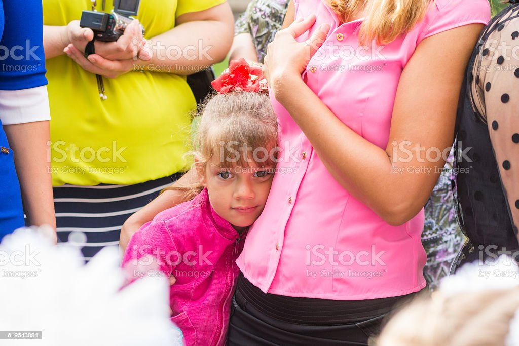 Five-year girl standing in crowd and clung to her mother stock photo