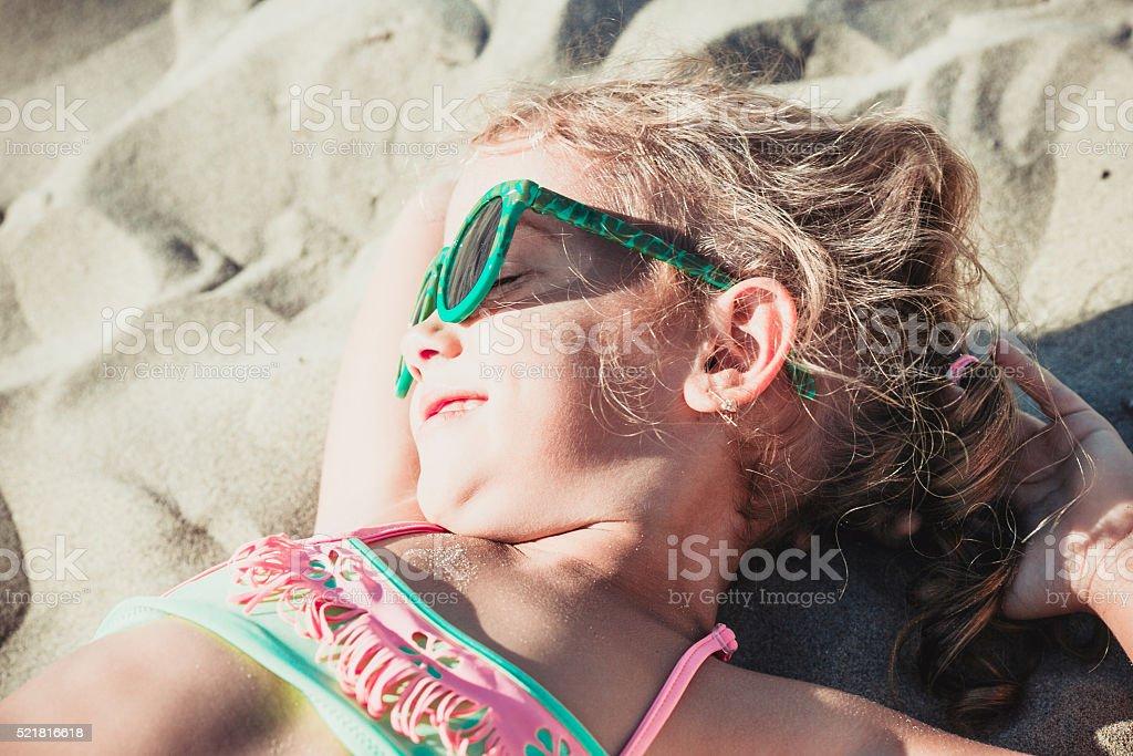 five-year-old girl is sunbathing stock photo