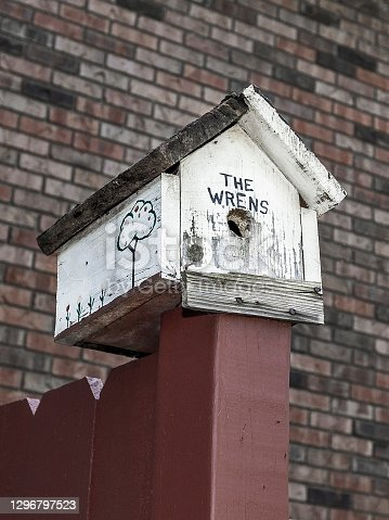 An old wooden wren birdhouse attached to the top of a fence post with blurred unfocused brick wall background. Copy space.