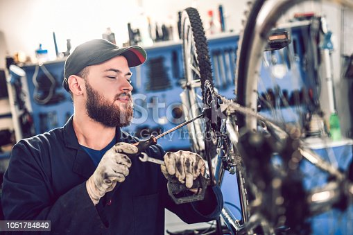 istock Fixing A Bike Chain Drive With Screwdriver 1051784840