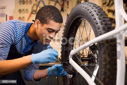 young mechanic fixing some gears on a bike