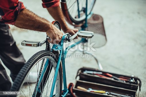 One mature man, repairing his bicycle outdoors alone, part of.
