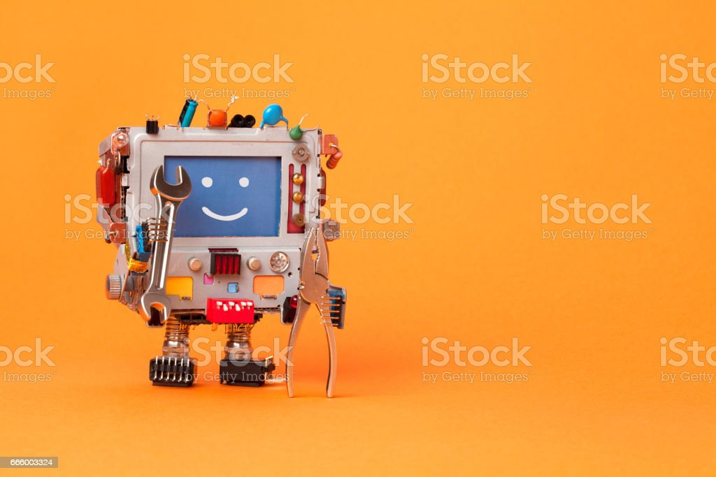 Fixing computer concept. Robotic electrician with hand wrenches for repair. Colorful display toy, smile message blue monitor. Service system communication concept. Orange background, copy space stock photo