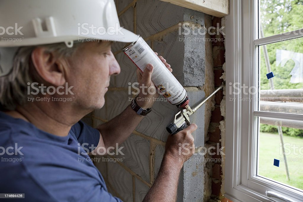 Fixing Double Glazing with Expanding Foam stock photo