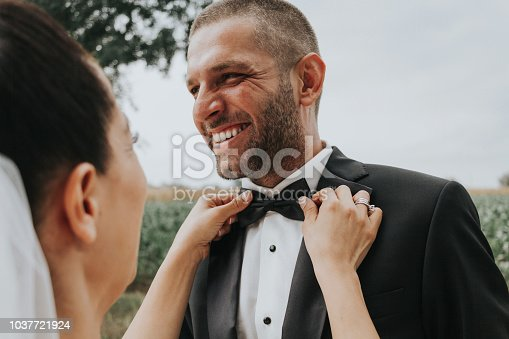 Fixing groom's bowtie at a wedding
