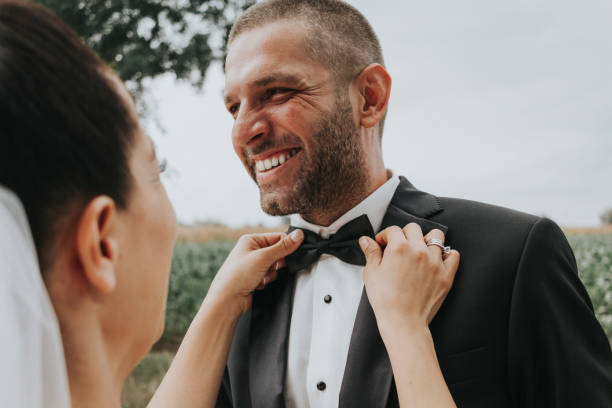 Fixing groom's bowtie at a wedding Fixing groom's bowtie at a wedding bridegroom stock pictures, royalty-free photos & images