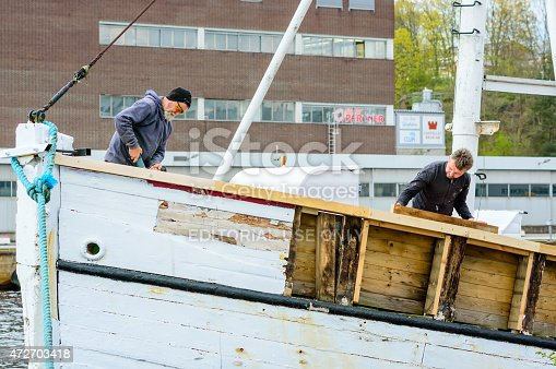 Karlshamn, Sweden - May 06, 2015: Two unknown workers renovate an old fishing boat in the harbor of Karlshamn. Persons work hard and boat is stripped of wood.