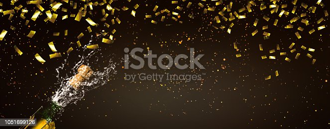 istock fizzing champagne and gold confetti 1051699126