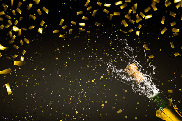 fizzing champagne in rainig gold confetti - anniversary stock pictures, royalty-free photos & images