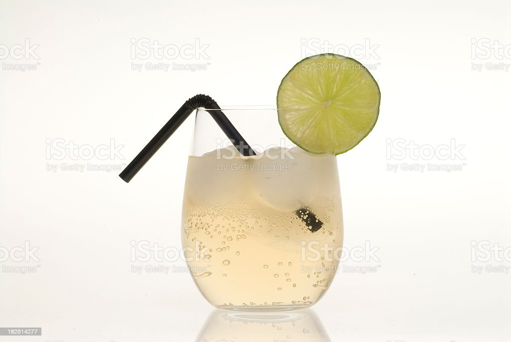 Fizzy ginger ale with lime and straw stock photo