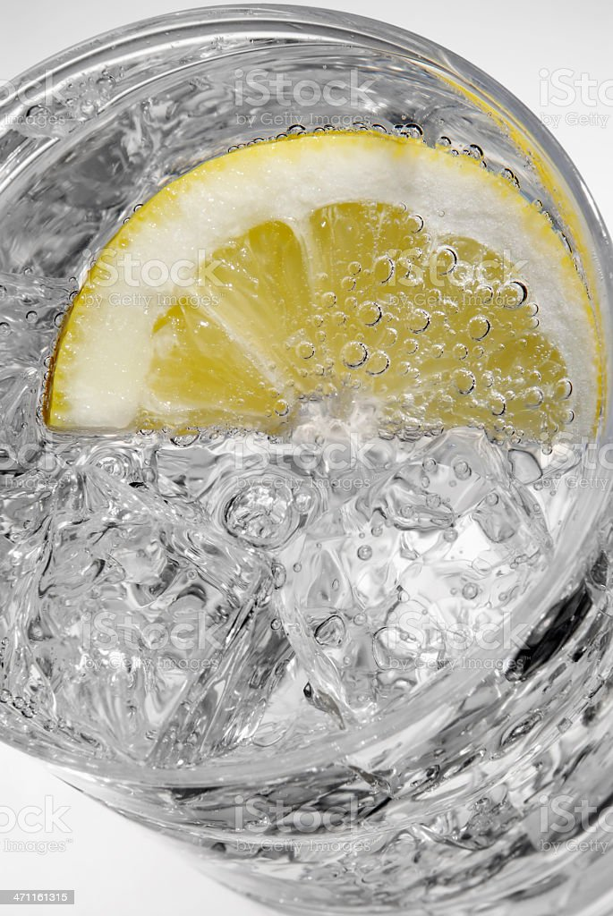 Fizzy mineral water with ice and a slice of lemon royalty-free stock photo