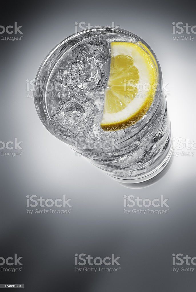 Fizzy mineral water with ice and slice of lemon royalty-free stock photo