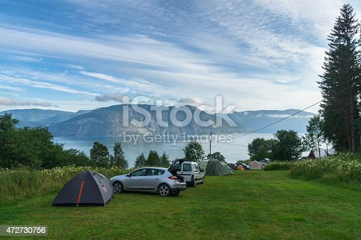 930810564 istock photo Fjord camping area with cars and tents 472730756