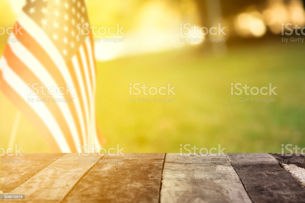 USA flag, afternoon sun along neighborhood road or meadow with blank table. stock photo