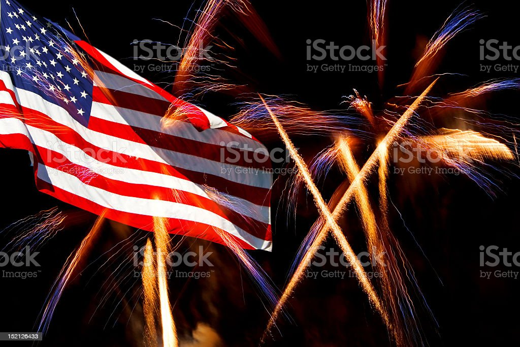 USA flag against backdrop of light streams of fireworks stock photo