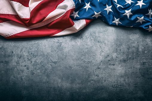istock USA flag. American flag freely lying on concrete background. 545427552