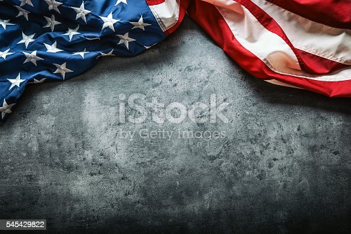 istock USA flag. American flag freely lying on concrete background. 545429822