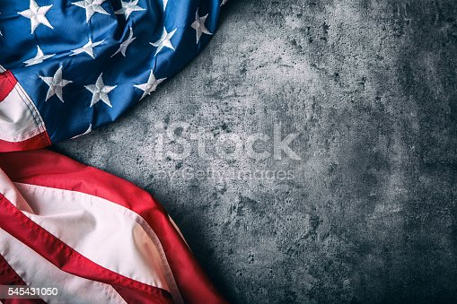 istock USA flag. American flag freely lying on concrete background. 545431050