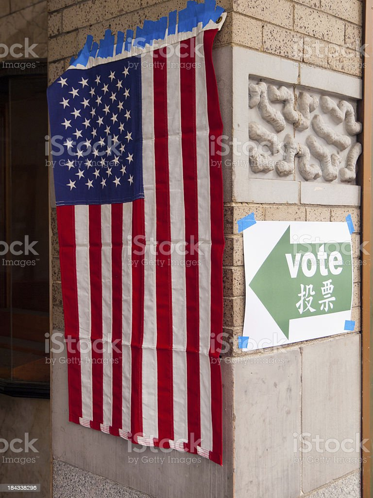 US flag and a sign pointing to polling booth stock photo