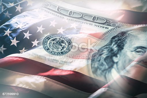 istock USA flag and American dollars. American flag blowing in the  wind and 100 dollars banknotes in the background 672599910