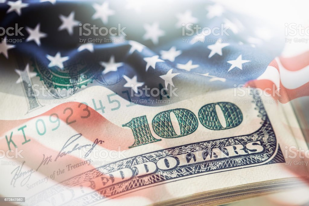 USA flag and American dollars. American flag blowing in the  wind and 100 dollars banknotes in the background USA flag and American dollars. American flag blowing in the  wind and 100 dollars banknotes in the background. American Flag Stock Photo