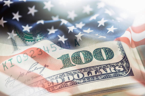 USA flag and American dollars. American flag blowing in the  wind and 100 dollars banknotes in the background stock photo