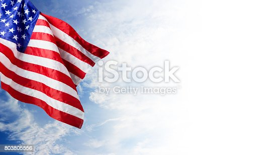 istock USA flag and blue sky with cloud background 803805556
