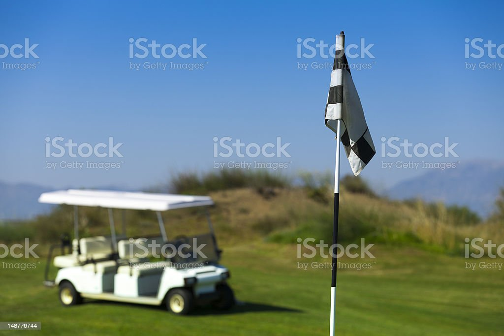 flag and cart on the golf course royalty-free stock photo