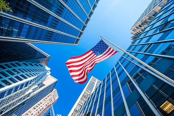 USA flag and contemporary glass skyscrapers in New York USA flag and contemporary glass architecture of Financial District, New York City, USA. manhattan financial district stock pictures, royalty-free photos & images