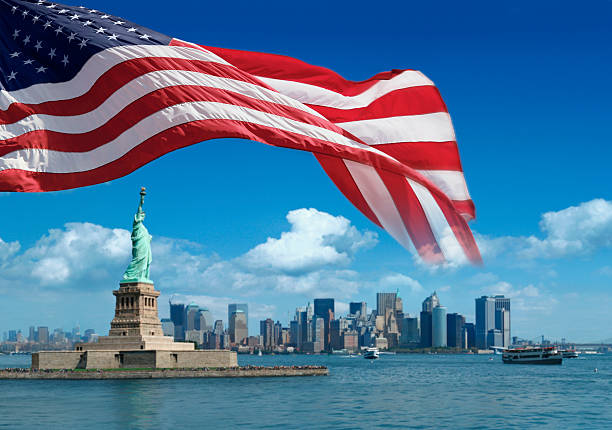 US flag and Statue of Liberty with New York behind stock photo