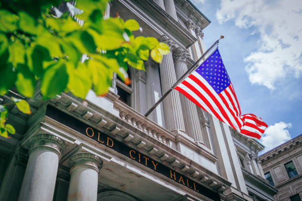 US Flag and the Old City Hall of Boston, USA Flag of United States flying over the entrance of Old City Hall in Boston, USA town hall stock pictures, royalty-free photos & images