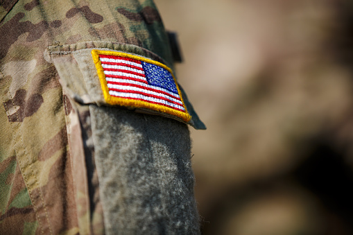 istock USA flag and US Army patch on solder's uniform 530944578