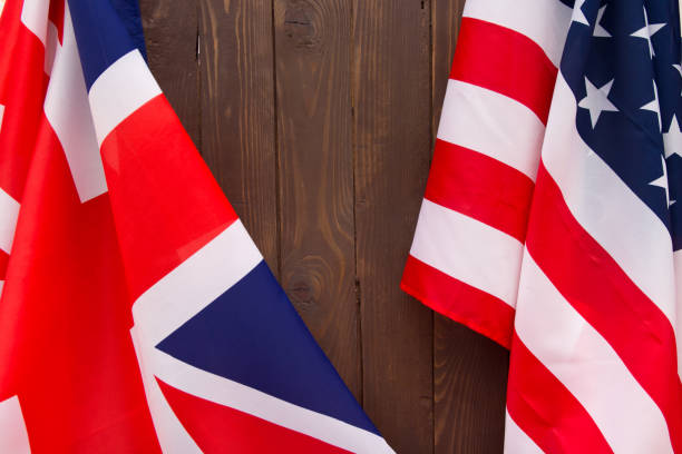 UK flag and USA Flag on wooden brown background. stock photo