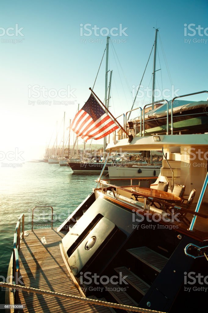 USA flag and yacht on sea, start of American journey stock photo