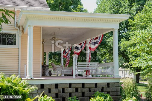 Traditional home with charming front porch decorated for the Fourth of July