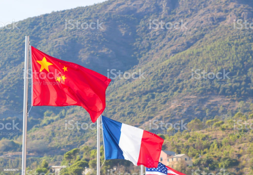 Flag, Chinese,French, American, Flag in a brisk breeze against a bright blue sky in summer background. stock photo