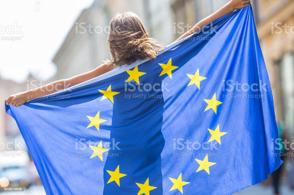 EU-Flagge. Niedliche glückliches Mädchen mit der Flagge der Europäischen Union. Junge Teenager-Mädchen winken mit der Flagge der Europäischen Union in der Stadt – Foto