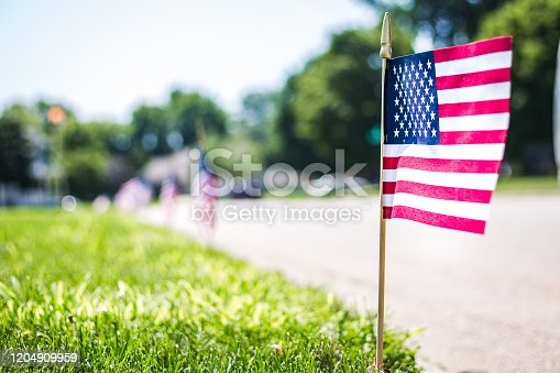 Small American flag, celebrating the Fourth of July, in a lawn in a small neighborhood.