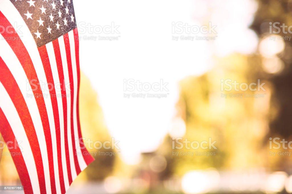 USA flag flies in afternoon sun along neighborhood road. stock photo