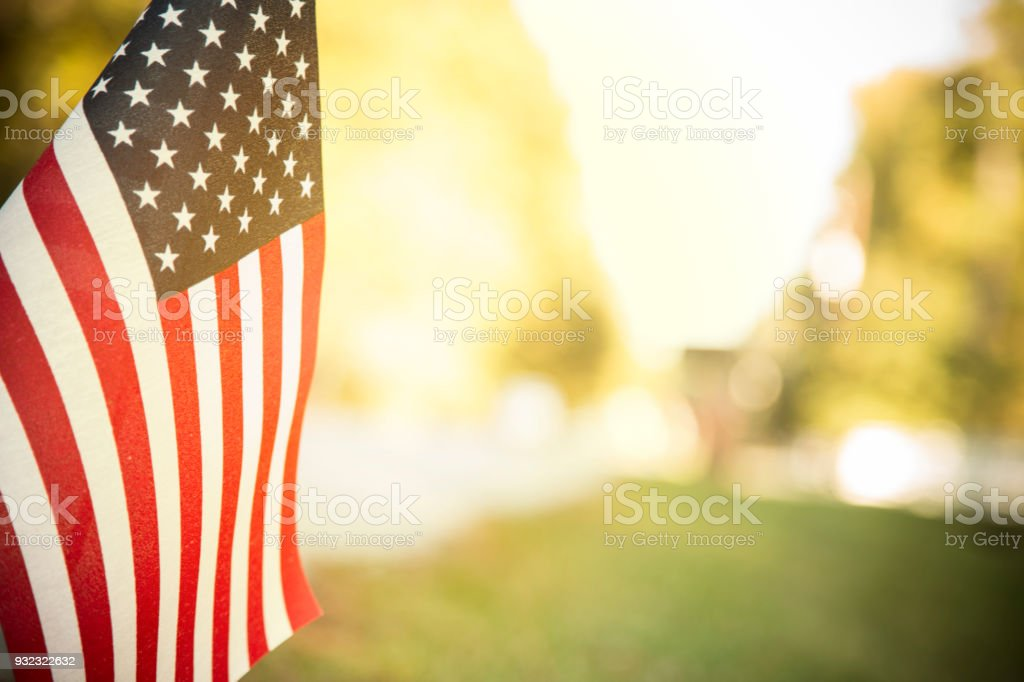 USA flag flies in afternoon sun along neighborhood road. USA flag flying along a neighborhood road with late afternoon sun shining through the fabric.  Trees line the street.  Copyspace. Agricultural Field Stock Photo