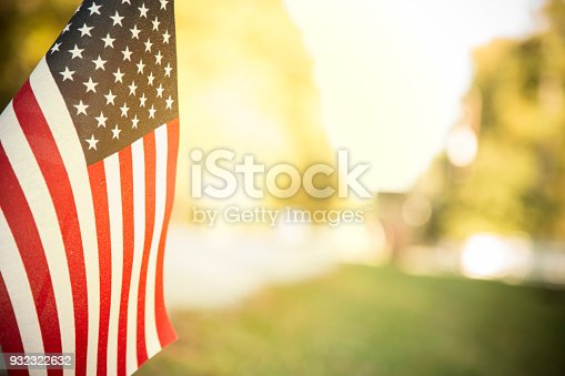 USA flag flying along a neighborhood road with late afternoon sun shining through the fabric.  Trees line the street.  Copyspace.