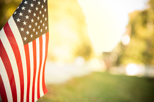 Usa Flag Flies In Afternoon Sun Along Neighborhood Road Stock Photo - Download Image Now