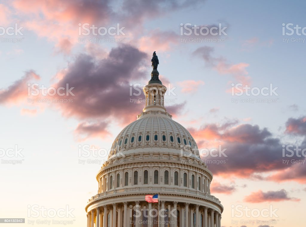 Flag flies in front of Capitol in DC at sunrise stock photo