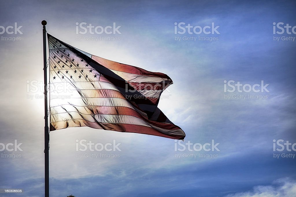 US Flag Fluttering in Backlit Blue Sky Symbolizing Government Transparency stock photo