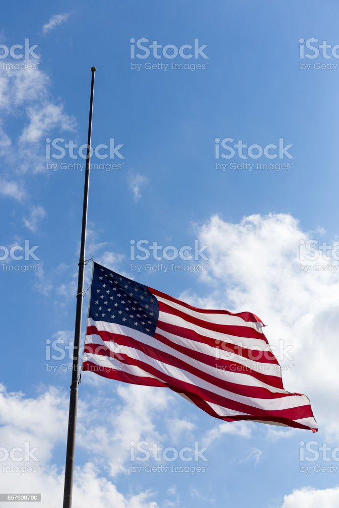 US flag flying half-staff stock photo
