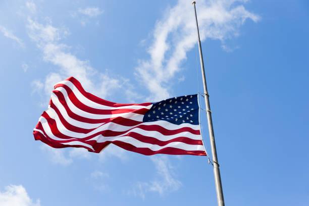 US flag flying half-staff stock photo