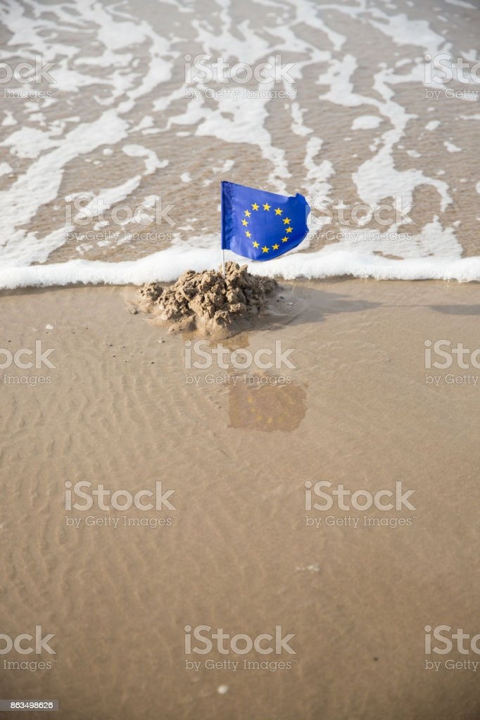 EEC Flag flying on a beautiful beach engulfed by waves stock photo