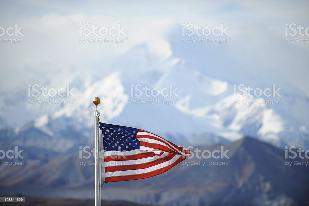 US flag flying with snowy Mount Mckinley in background stock photo